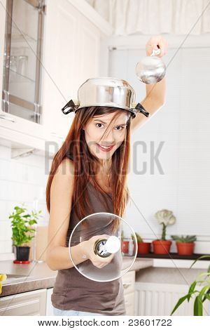 Kitchen Knight - young beautiful caucasian woman in kitchen with pot on her head (as helmet) and hohl (as sword)