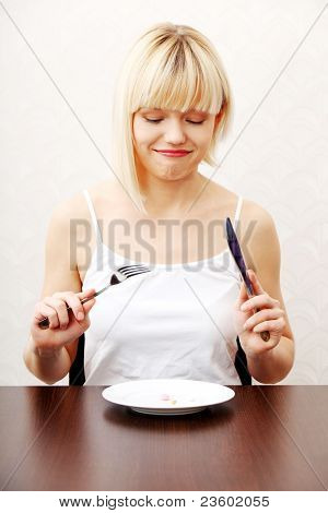 Woman eating nutritional supplement - pills on plate.