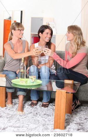 Young women drinking wine on a sofa