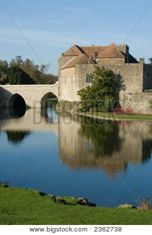 Old English Castle And Moat With Feeding Swans
