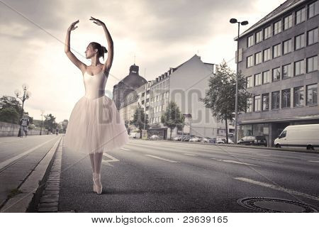 Beautiful ballerina dancing on a city street