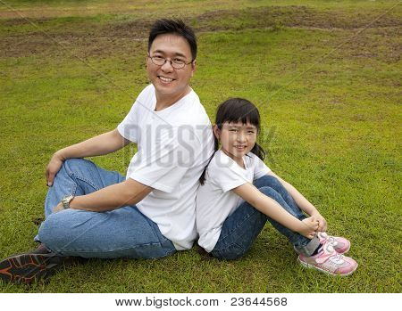 happy father with daughter sitting on the grass