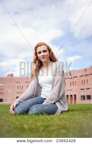 Portrait Of A Young Woman Sitting On A Lawn