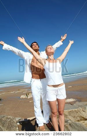 Couple doing yoga exercises on the beach