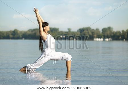 Outdoor Portrait of Beautiful Young Woman Doing Yoga in Water