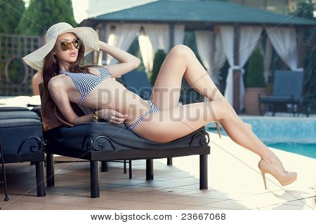 Beautiful Woman Resting Poolside at Luxury Resort in Sun Hat