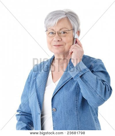 Elderly lady standing over white background, talking on mobile phone, smiling.?