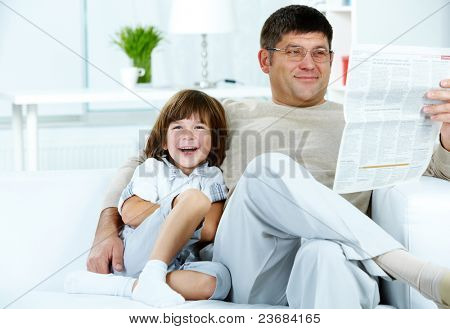 Photo of happy boy sitting by his father reading paper at home