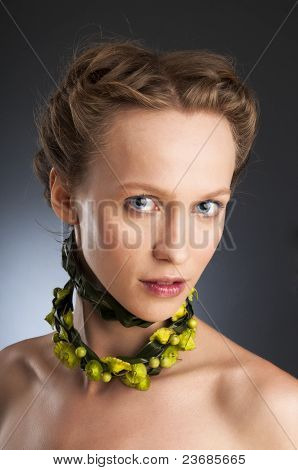 Attractive girl portrait with floristic necklace.