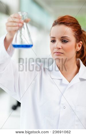 Portrait of a science student looking at a blue liquid in an Erlenmeyer flask