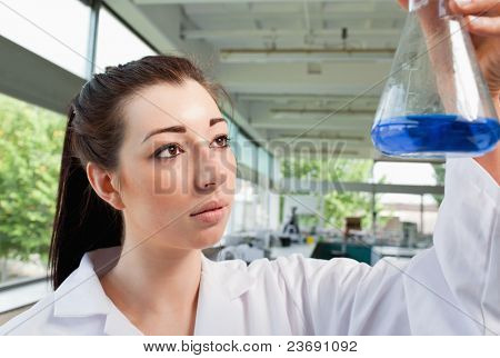 Brunette looking at an Erlenmeyer flask in a laboratory