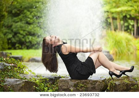 smiling woman sitting at pond