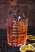 Grains Of Coffee Fall Into A Glass With A Drink. A Glass With Whiskey On A Wooden Background. Close- poster