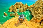 Tourism In Algarve. Summer Holidays In Portugal, Europe. Lifestyle Tourist Sitting On Promontory Of  poster
