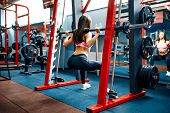 Athletic Young Sporty Woman Doing Squat Exercise In The Smith Machine. Smith Rack Machine In Modern  poster