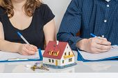Divorce And Dividing A Property Concept. Man And Woman Are Signing Divorce Agreement. poster