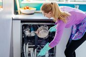Young Woman Putting Dirty Dishes To Dishwasher poster