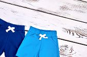 Kids Summer Colored Shorts. New Kids Cotton Shorts On White Wooden Background. Childs Casual Outfit  poster