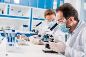 Selective Focus Of Scientists In Medical Masks Working In Lab Together poster