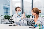 Scientists In White Coats, Medical Masks And Goggles Giving High Five To Each Other In Lab poster