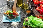 Man Preparing Salad With Fresh Vegetables On A Wooden Table. Cooking Tasty And Healthy Food. On Blac poster