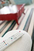 Using White Remote Control. Program Switching Or Button Pressing On Tv Keypad. Bright Living Room. poster