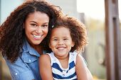 Mixed race mother and young daughter smile to camera outside poster