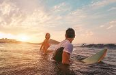 Fit Couple Surfing At Sunset - Surfers Friends Having Fun Inside Ocean - Extreme Sport, Travel, Heal poster
