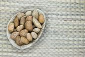 Almonds With The Nutshell In Eco Natural Banana Leaf Plate On Natural Bamboo Mat Surface With Free S poster