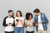 Photo of emotional group of friends standing isolated over grey wall background using mobile phones  poster