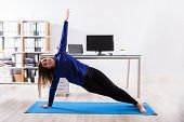 Young Businesswoman Doing Stretching Exercise On Exercise Mat At Workplace poster