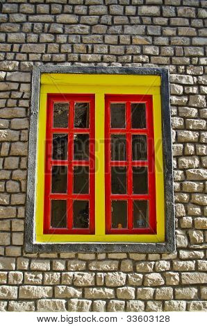 yellow window on brick wall