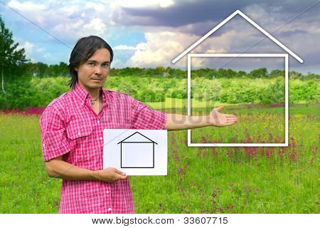Young Man Holding A White Board With  House On A Green Meadow