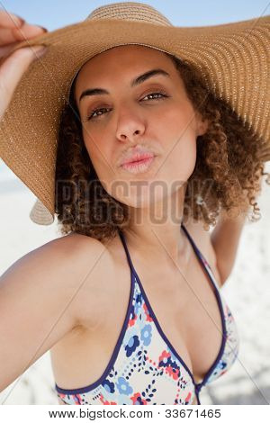 Young woman puckering her lips while holding her hat brim in front of the camera