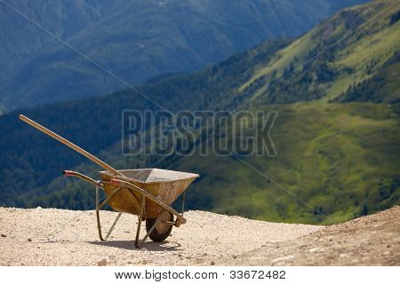 Empty wheelbarrow in mountain landscape