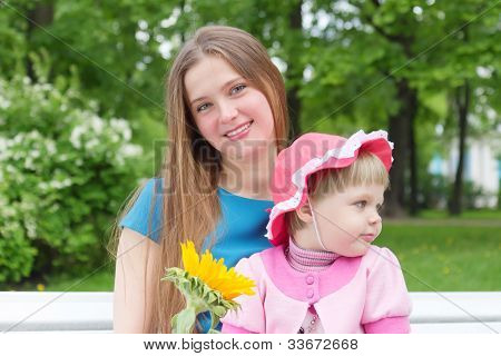 Little Girl And Young Mother In A Park