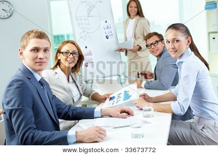 Image of confident partners looking at camera during presentation
