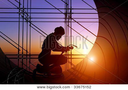 A silhouette of a worker-welder.