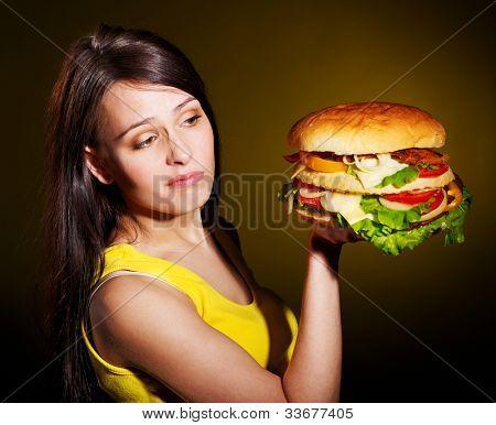 Slim woman holding hamburger.