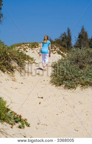 Teen Girl Walking Up Sand Dune