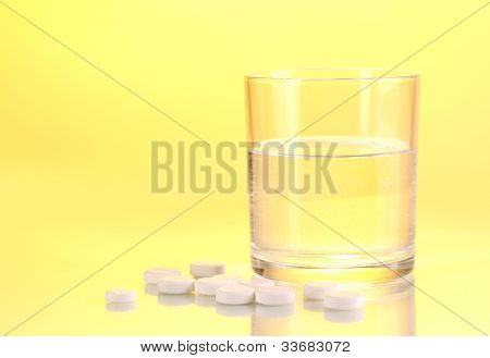 Glass of water and pills on yellow background