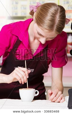 Friendly waitress making coffee at coffee machine