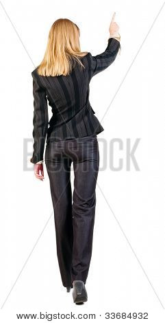 back view of walking business woman.  pointing young girl in black suit. Rear view people collection.  backside view of person.  Isolated over white background.