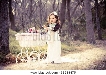 Cute girl in vintage clothes with flowers in pram