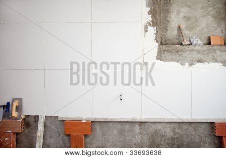 tiles white wall contruction with trowels tools and bricks