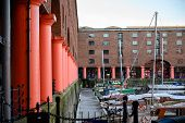 Moored Boats And The Red Pillars Of The Albert Dock In Liverpool poster