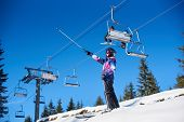 Female Skier Smiling Standing On Mountain Slope Near Ski Lift Hoist. Woman In Ski Goggles Showing Wi poster