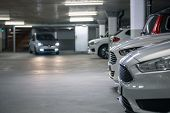 Underground parking. Cars parked in a garage with no people. Many cars in parking garage interior. U poster