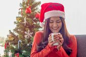 Beautiful Asian Woman In A Santa Claus Hat Is Sitting On The Sofa, Holding A White Cup And Happy To  poster