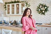 Woman At Home For Christmas. Woman Preparing At Home. Smiling Woman In Pink Dress In Kitchen. White poster